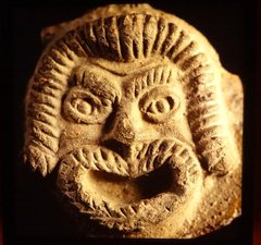 Pottery lamp detail showing a theatrical mask