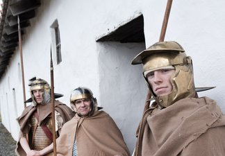 3 Roman soldiers stand outside barrack block