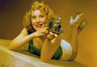 View of the model, Irene Warren, posing with a film camera for a Turners publicity shot, January 1957 (