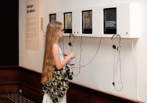 Girl listening to audio recording in gallery